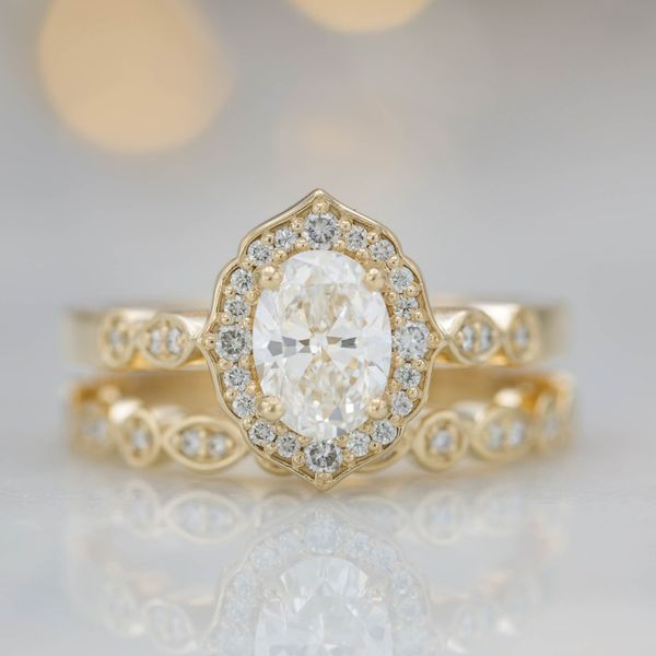 0.8ct oval diamond in a classic, vintage-inspired floral halo with a matching scalloped wedding band.