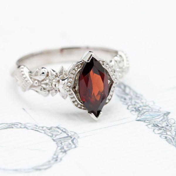 Gothic elegance with the beadwork around this skull ring and the blood-red pop of color of the garnet center stone.