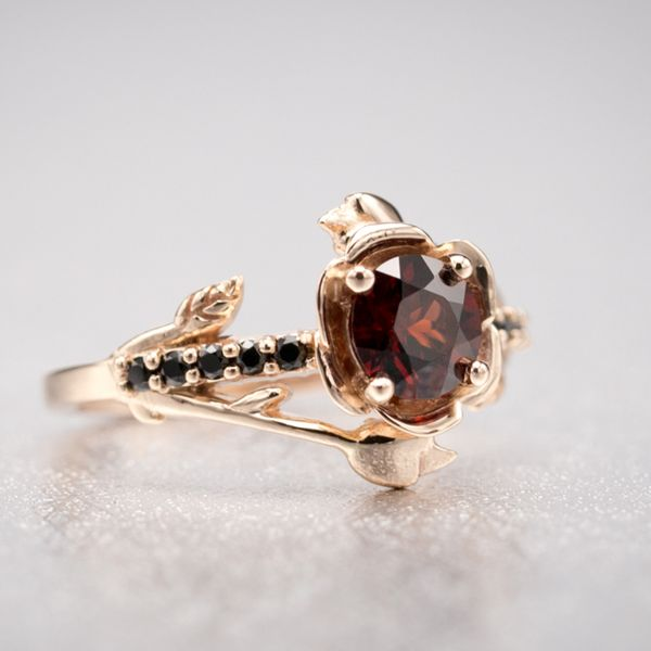Stunning delicate rose setting in rose gold with a deep Mozambique red garnet accented by black spinel.