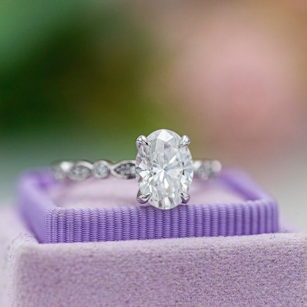 This solitaire engagement ring sets an oval diamond with claw prongs on a diamond-studded scalloped band.