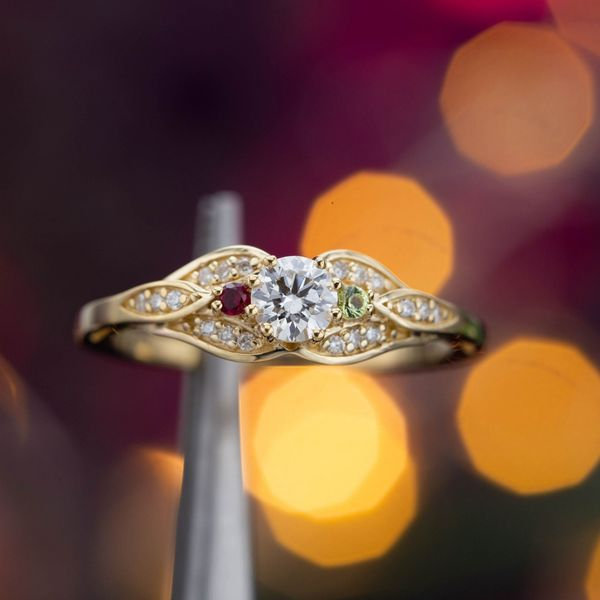A delicate, low-profile ring with peridot and ruby birthstone accents tucked into the split, pave shank.