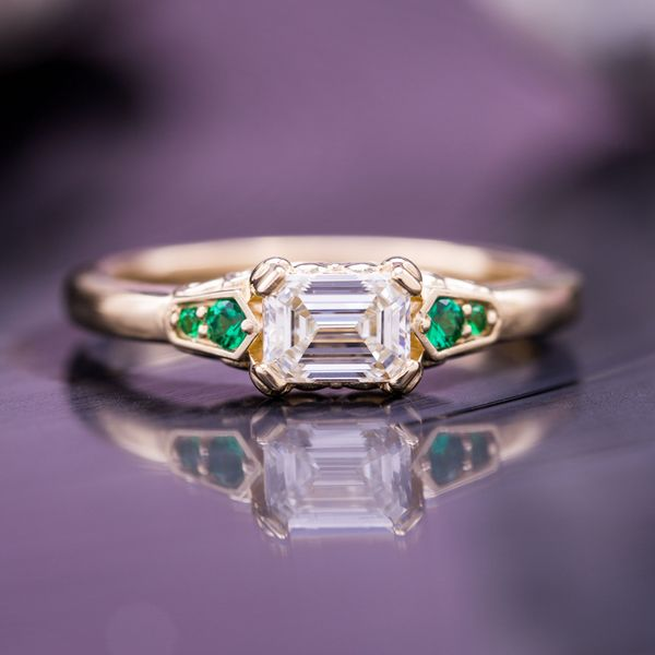 East-west set emerald cut diamond with emerald accents.