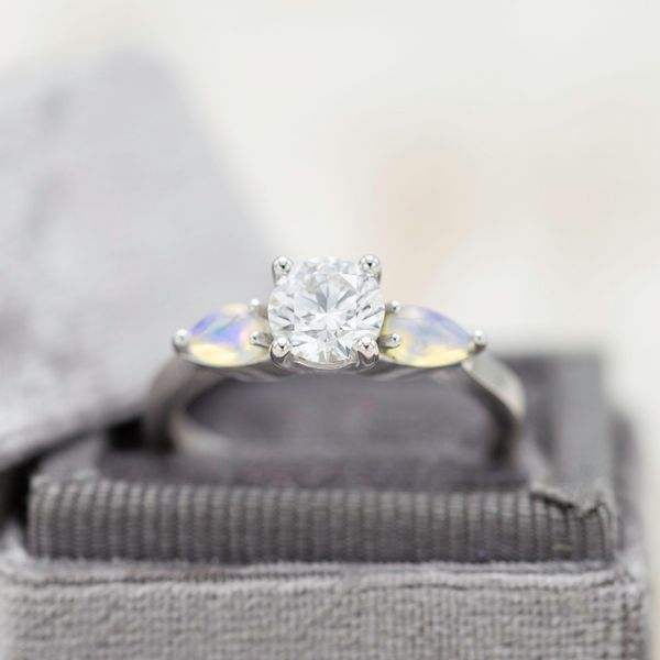 A classic three-stone setting uses pear cut white opals around the diamond center stone to add a distinctive shimmer.