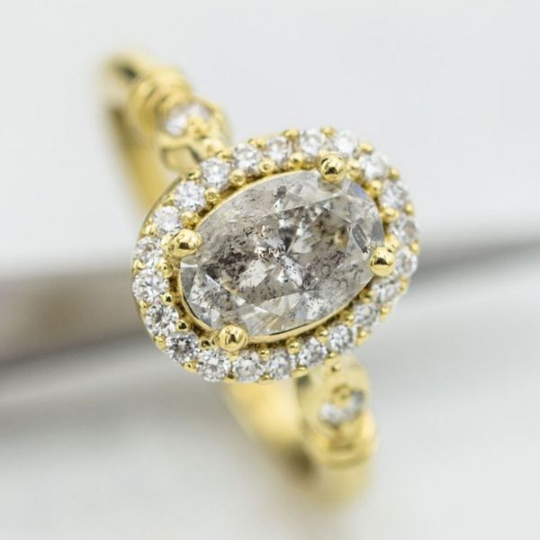 A salt-and-pepper oval diamond set off by its bright diamond halo and a vintage-inspired gold shank.