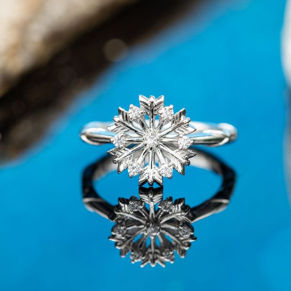 A white gold snowflake ring sets a small cluster of diamonds instead of a single center stone.