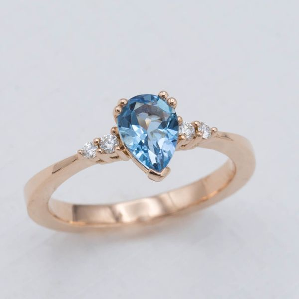 A delicate rose gold band with a reverse taper from the pear cut aquamarine center stone.