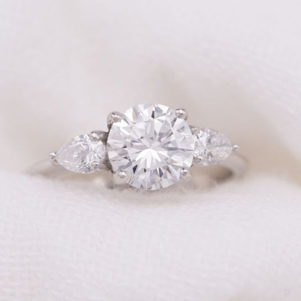 1.02ct round cut diamond with pear cut diamond side stones in a tapered platinum ring. A perfectly curved 3-stone ring.