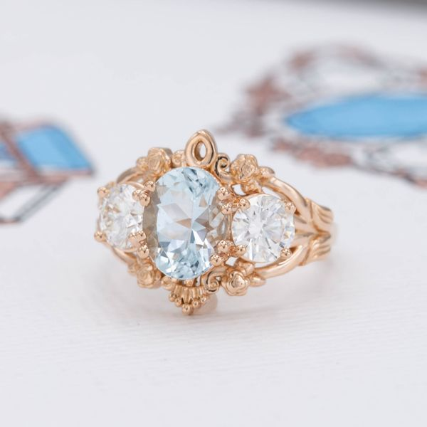A bold, vintage-inspired engagement ring sets an aquamarine and half-carat diamonds in an intricate, floral rose gold design.