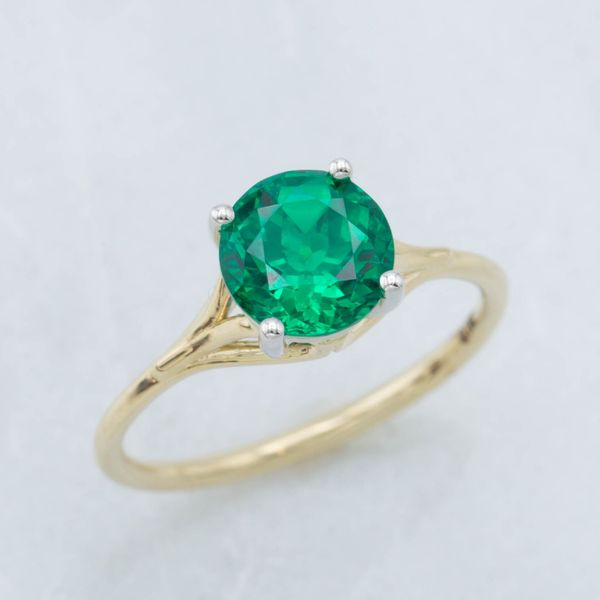 Delicate yellow gold setting with elegant curves setting a lab-created round emerald.