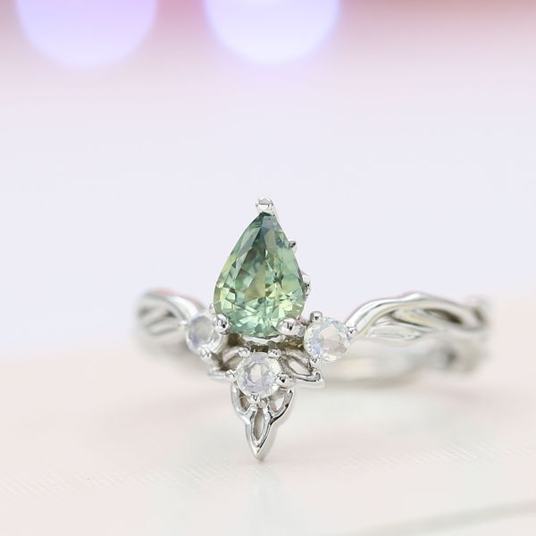 A minty green sapphire engagement ring with a vining tiara inspiration and moonstone accents.