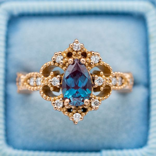 Vintage engagement ring in rose gold with a pear cut alexandrite and diamond accents.