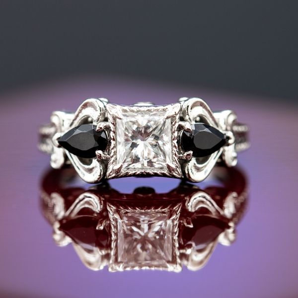 Pear cut black diamonds accent the princess cut center stone in this wonderfully ornate ring.