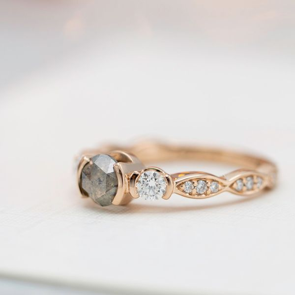 The colors in this ring blend beautifully, as do the vintage elements (a scalloped band and rose cut diamond) and the modern choices (the semi-bezel settings and the moody gray of salt & pepper diamond).