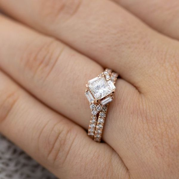 Baguette diamonds trace the outer edges of the kite set princess cut diamond in this modern ring.