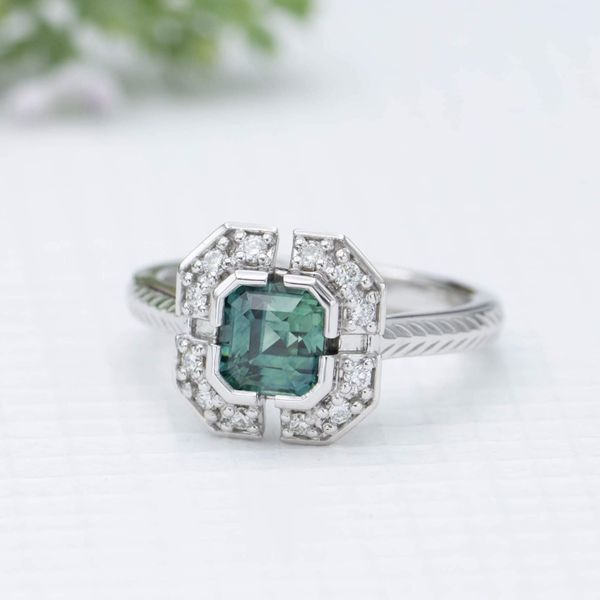 Inspired by Art Deco geometry, we designed this ring with small gaps for a unique look around a perfect blue-green sapphire center stone.