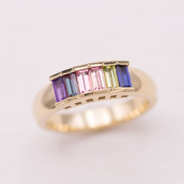 This step ring features two pink tourmaline baguettes surrounded by alexandrite, amethyst, peridot, and sapphire.