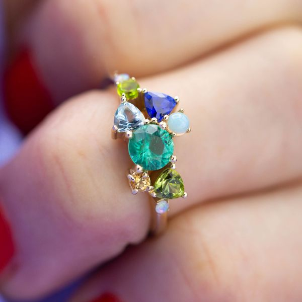 An open, modern, asymmetric cluster, blending trillion and round cut gems in shades of blue, yellow, and green.