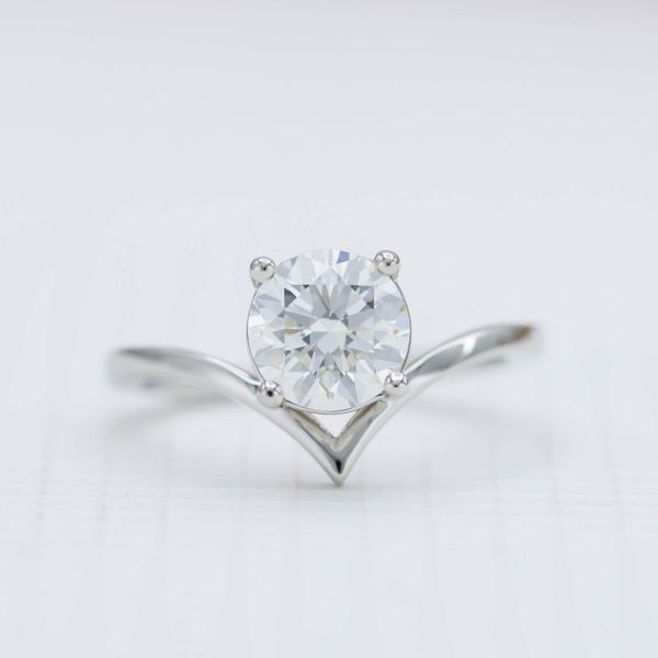 1.40ct round cut diamond nestles into the elegant curve of a delicate platinum band.