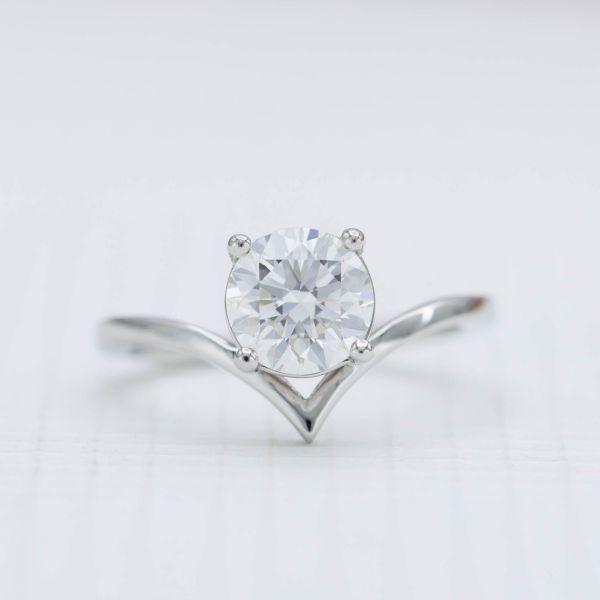 1.40ct round cut diamond nestles into the elegant curve of a delicate platinum band.
