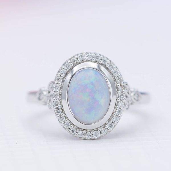 The bezel setting in this modern halo ring protects the white opal and adds a sleek design element to the ring.