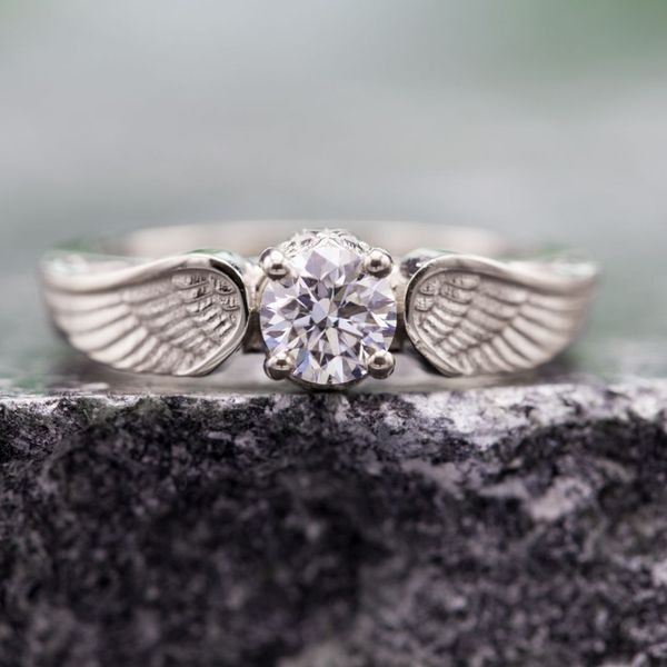 An elegant interpretation of the snitch from Harry Potter using angelic wings around the center stone.