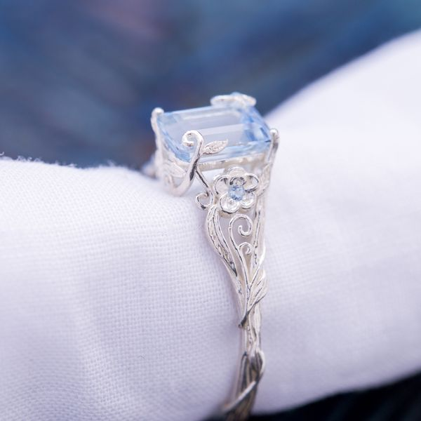 An impossibly delicate floral setting sees the vines curl up and around the emerald cut aquamarine center stone.