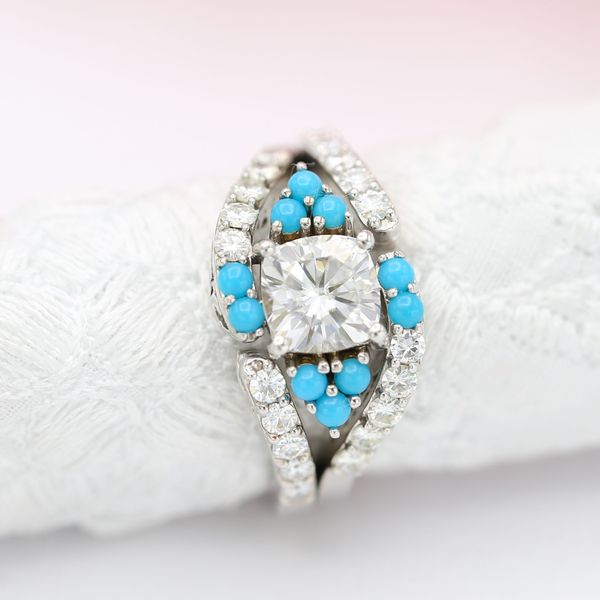 This diamond engagement ring surrounds a beautiful cushion cut diamond with turquoise accents for a distinctive twist.