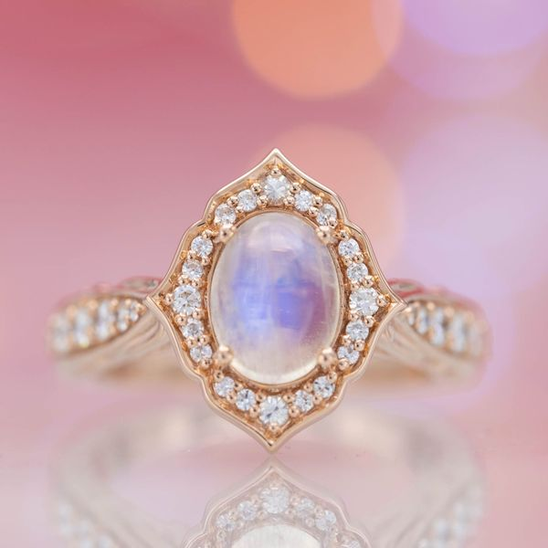 A delicately curving antique frame halo of diamonds surrounds an oval moonstone center stone.