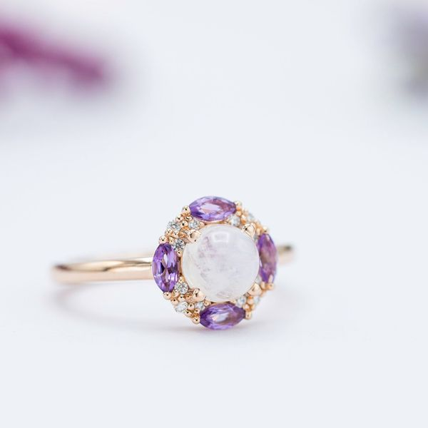 Moonstone engagement ring with a unique halo of marquise amethysts and diamonds.