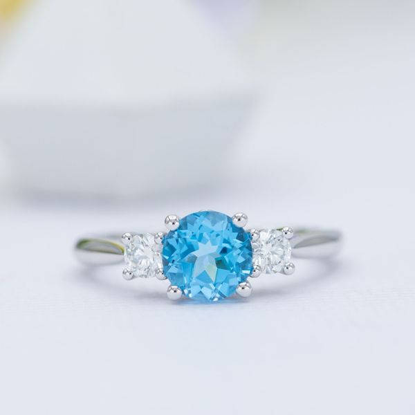 Three-stone engagement ring with Swiss blue topaz and diamonds.