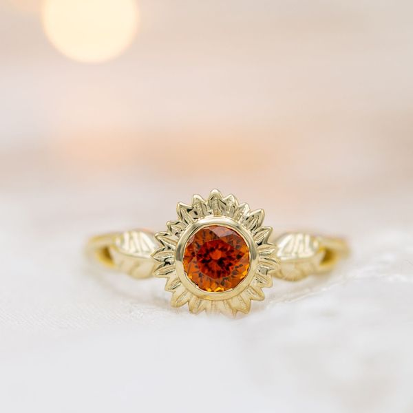 A gold sunflower engagement ring with the warm, vibrant orange of spessartite garnet at its center.