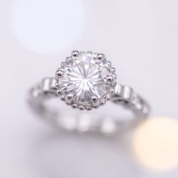 Scroll-shaped cathedral shoulders surround a scalloped setting for a large, round moissanite.