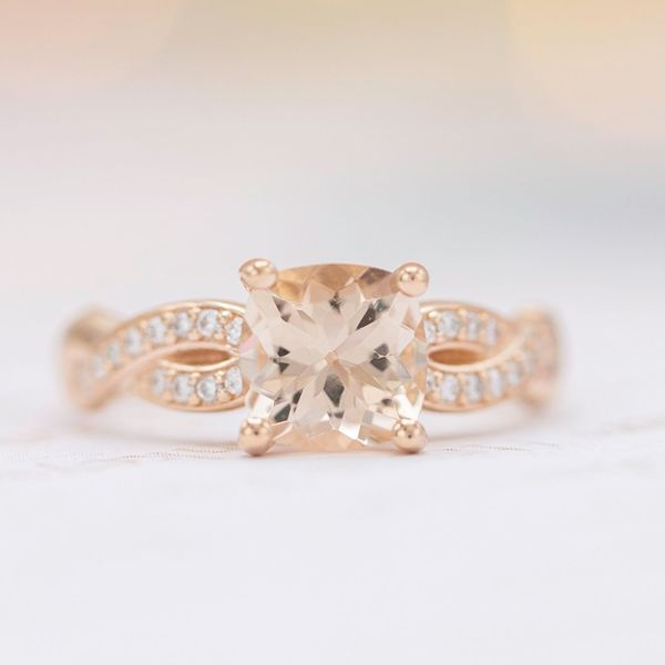 This ring features a peach cushion cut morganite centerpiece on a diamond pave band.