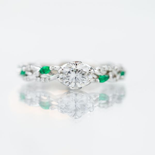 East-west set oval moissanite on a delicate vining band with emerald and moissanite accents.