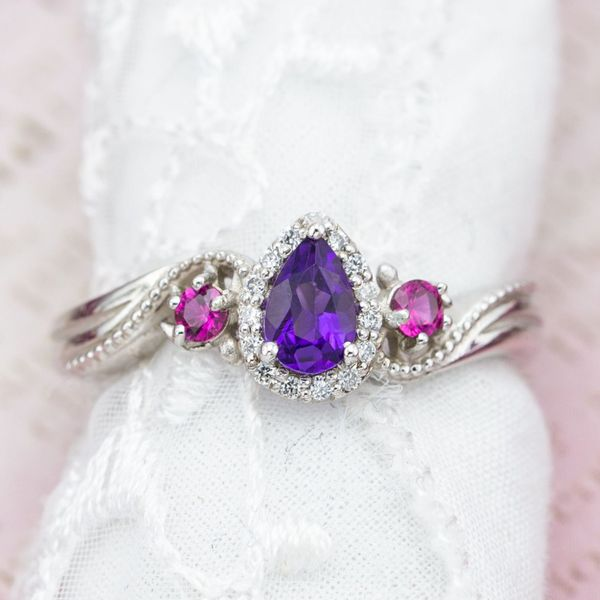 An elegant amethyst and pink sapphire ring with subtle turtle settings for the sapphires.