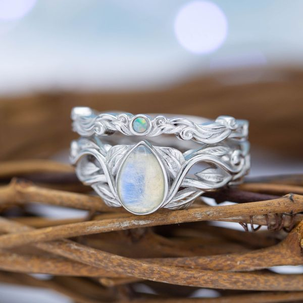 This nature-inspired bridal set features a pear cut moonstone and a small white opal with similar coloring on the matching band.