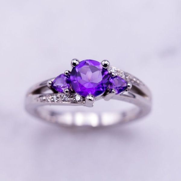 In this three-stone ring, royal purple amethyst contrasts beautifully with the white gold and diamonds around it.
