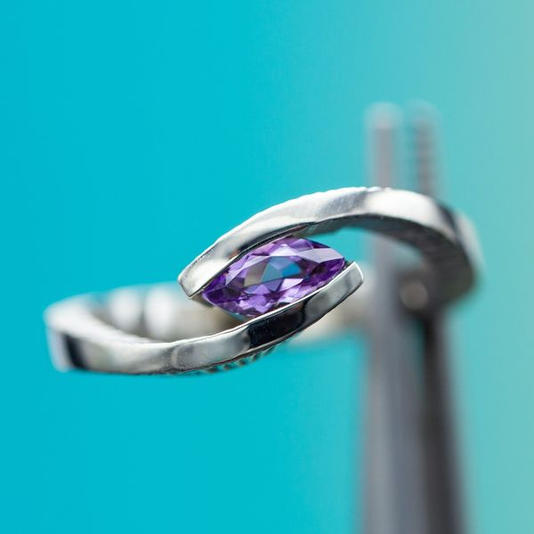 This faux-tension setting uses a hidden rail to create the illusion of a center stone suspended in the bypass setting.
