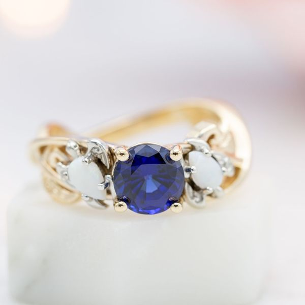 Sapphire and white opals in a three stone ring with white gold turtle settings for the side stones.