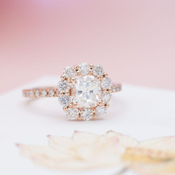 Using larger halo diamonds in this mostly modern engagement ring balances the look with a touch of vintage styling.