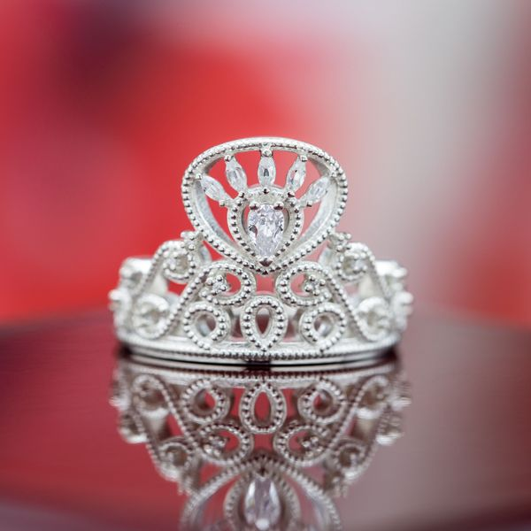 A tall crown design with a pear cut center stone, marquise cut accents, and bead detailing.