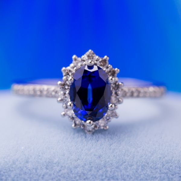 Inspired by the famous royal ring worn by Princess Diana and later Kate Middleton, this engagement ring features a deep blue sapphire center stone surrounded by a sunburst diamond halo. We incorporated pave diamonds on the white gold shank to complete the perfect look for this couple.