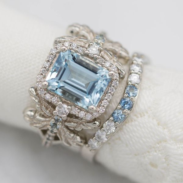 This dragonfly keeps the bold, sculptural design in balance with a Caribbean blue emerald cut aquamarine. The halo and a delicately curved aqua and diamond band give the rings timeless sparkle.