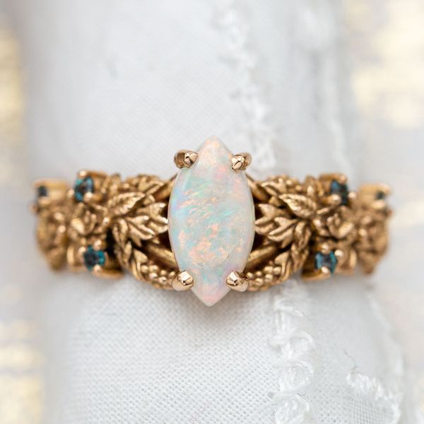 This ring's intricate nature-inspired detail serves as a backdrop to the opal's bright colors.