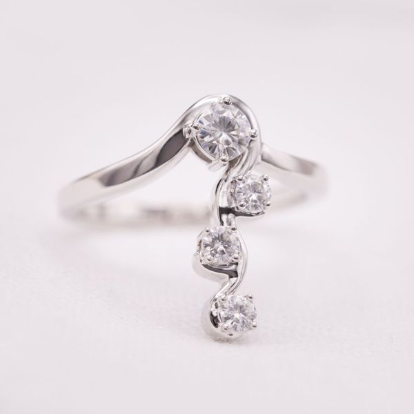 This unusual, modern ring makes a statement by setting a small group of diamonds along the length of the finger.