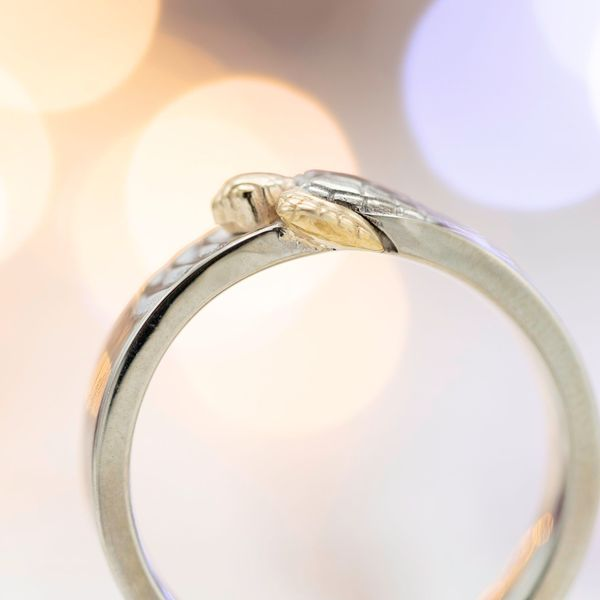 Mixed metals highlight the details of the turtle on this wedding band.