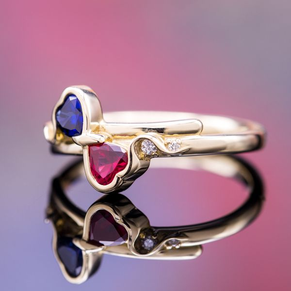 A play on a two-stone toi-et-moi setting with natural curves tracing the setting for sapphire and ruby hearts.