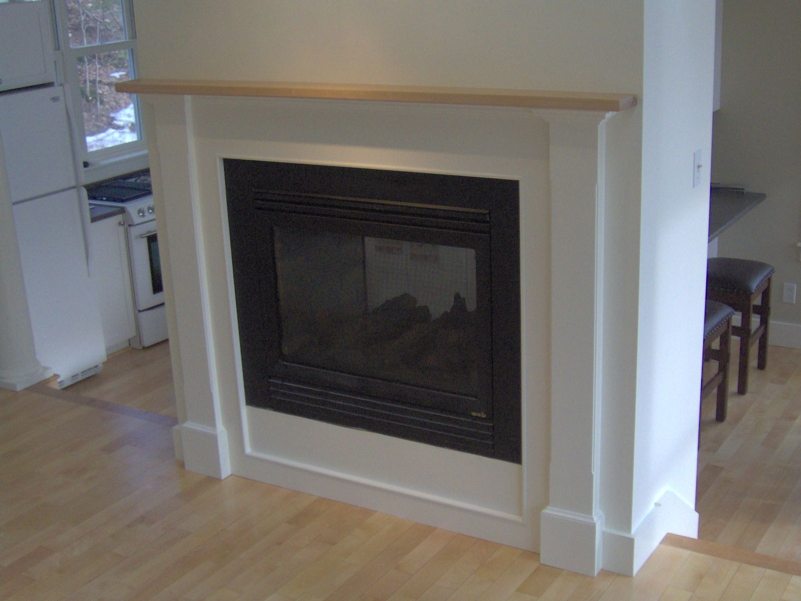 This surround is part of a two sided gas fireplace.  One side at floor level and the other at counter height from the step down kitchen/dining area.  …