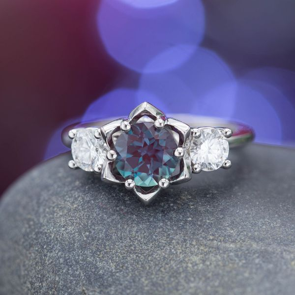 Subtle, lotus-inspired petals create a sort of halo around the alexandrite in this three-stone ring with diamonds.