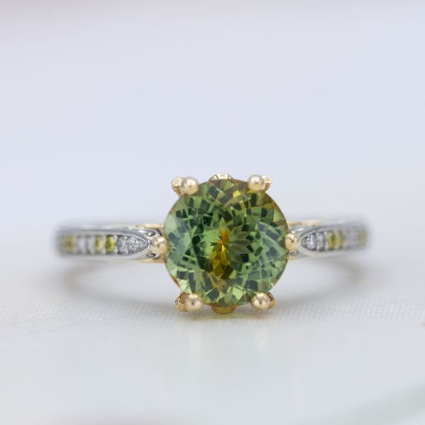The gold basket of this engagement ring brings out yellow hues in the bright green sapphire center stone.